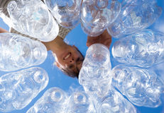 Smiling woman recycling plastic water bottles. Looking up POV in New Zealand, NZ Royalty Free Stock Image
