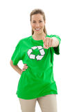 Smiling woman in recycling symbol t-shirt pointing at camera. Smiling young woman in recycling symbol t-shirt pointing at camera over white background Royalty Free Stock Photos