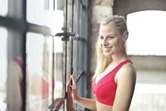 Smiling Woman In Red Brassiere Near Glass Window Royalty Free Stock Image