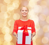 Smiling woman in red clothes with gift box Stock Photo