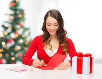 Smiling woman in red clothes with postcard Royalty Free Stock Photo