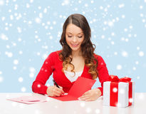 Smiling woman in red clothes with postcard Royalty Free Stock Photos
