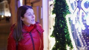 Smiling woman in red coat standing near window-shop decorated with Christmas tree and garlands. Beautiful smiling woman in red coat standing near window-shop stock video footage