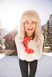 Smiling woman with red cup standing near cosy mountain house Royalty Free Stock Photography