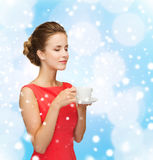 Smiling woman in red dress with cup of coffee Stock Images