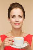 Smiling woman in red dress with cup of coffee Stock Image