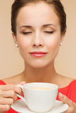Smiling woman in red dress with cup of coffee Royalty Free Stock Images