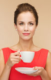Smiling woman in red dress with cup of coffee Stock Photography