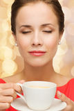 Smiling woman in red dress with cup of coffee Royalty Free Stock Photography
