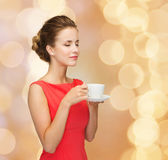 Smiling woman in red dress with cup of coffee Royalty Free Stock Image