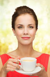 Smiling woman in red dress with cup of coffee Royalty Free Stock Photos