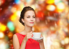 Smiling woman in red dress with cup of coffee Stock Photos