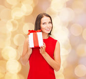 Smiling woman in red dress with gift box. Christmas, holidays, valentine's day, celebration and people concept - smiling woman in red dress with gift box over Stock Photos
