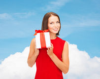 Smiling woman in red dress with gift box. Christmas, holidays, valentine's day, celebration and people concept - smiling woman in red dress with gift box over stock image