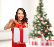 Smiling woman in red dress with gift box. Christmas, x-mas, valentine's day, celebration concept - smiling woman in red dress with gift box Royalty Free Stock Image