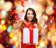 Smiling woman in red dress with gift box Royalty Free Stock Images