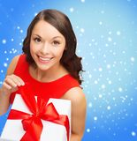 Smiling woman in red dress with gift box Stock Photo