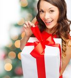 Smiling woman in red dress with gift box Royalty Free Stock Photos