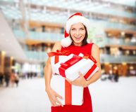 Smiling woman in red dress with gift boxes Stock Image