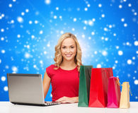 Smiling woman in red dress with gifts and laptop. Christmas, holidays, technology, advertising and people concept - smiling woman in red blank shirt with Stock Photos