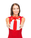 Smiling woman in red dress holding gift box Royalty Free Stock Photo