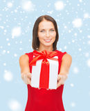 Smiling woman in red dress holding gift box Stock Photos