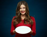 Smiling woman in red dress. Holding white empty plate Stock Images
