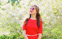 Smiling woman in red dress looks with hope up over spring flowering garden Stock Photo