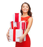 Smiling woman in red dress with many gift boxes stock photo