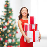 Smiling woman in red dress with many gift boxes Royalty Free Stock Image