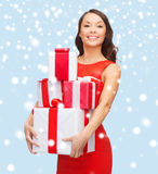 Smiling woman in red dress with many gift boxes Royalty Free Stock Photo
