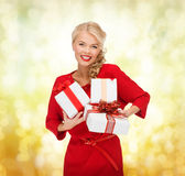 Smiling woman in red dress with many gift boxes Royalty Free Stock Images