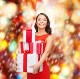 Smiling woman in red dress with many gift boxes Royalty Free Stock Photos