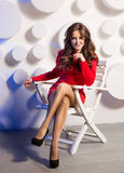 Smiling woman in red dress posing on white wooden chair Royalty Free Stock Photos