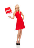 Smiling woman in red dress with sale sign Stock Photo