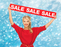 Smiling woman in red dress with sale sign Royalty Free Stock Photography