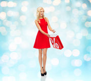 Smiling woman in red dress with shopping bag Royalty Free Stock Photo