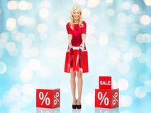 Smiling woman in red dress with shopping bags Stock Photography