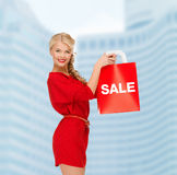 Smiling woman in red dress with shopping bags Royalty Free Stock Photos