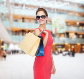 Smiling woman in red dress with shopping bags Stock Images