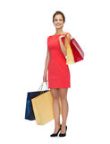 Smiling woman in red dress with shopping bags Royalty Free Stock Image