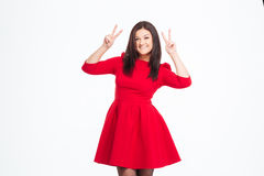 Smiling woman in red dress showing two fingers sign Stock Photo