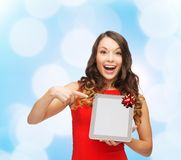 Smiling woman in red dress with tablet pc. Christmas, technology, present and people concept - smiling woman in red dress with blank tablet pc computer screen Stock Photo