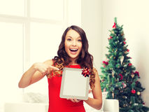 Smiling woman in red dress with tablet pc. Christmas, technology, present and people concept - smiling woman in red dress with blank tablet pc computer screen Stock Photography