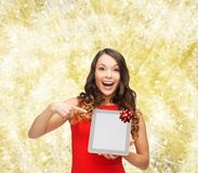 Smiling woman in red dress with tablet pc. Christmas, technology, present and people concept - smiling woman in red dress with blank tablet pc computer screen Royalty Free Stock Photo