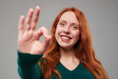 Smiling woman with red hair giving a thumbs up gesture stock photography