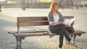 Smiling woman with red hair sitting on a bench with coffee and reading newspaper, sunny day stock footage