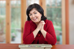 Smiling woman in red knitted jacket sitting at the desk Stock Photography