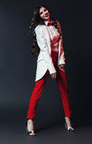 Smiling woman in red pants and white coat Stock Photography