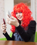 Smiling woman in red periwig. Stares into mirror at home Stock Photography